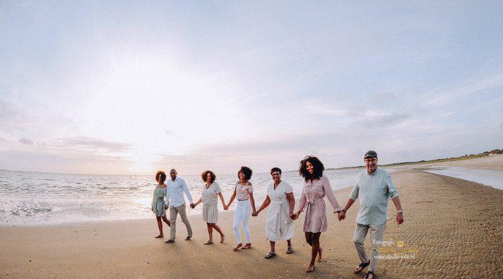 Familie groepsfoto laten maken op het strand